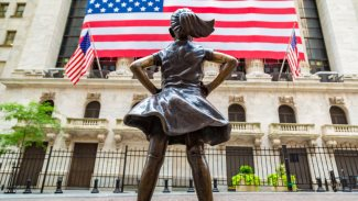 Fearless Girl Statue looking up at New York Stock Exchange building at Wall Street in Manhattan, New York City, USA