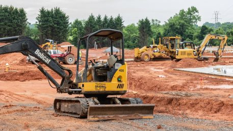 Earth--moving machinery prepares building site for apartment complex