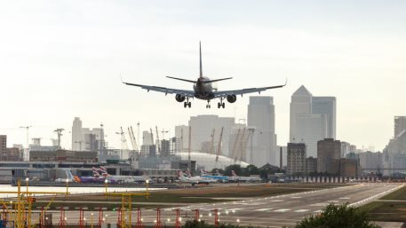 British Airways airplane landing at London City Airport with Canary Wharf business district in the background