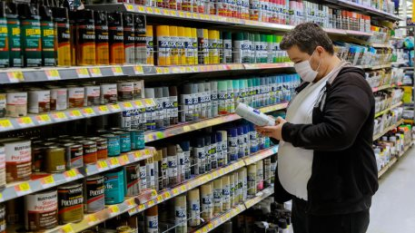 A man wearing a protective mask in buyer selects paint