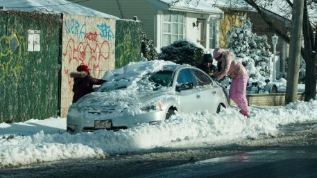 DECEMBER 17, 2020: Family cleans car from snow in Brooklyn, NY after massive Winter Storm Gail