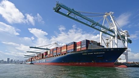 Container ship loads cargo containers under gantry cranes at Port Miami