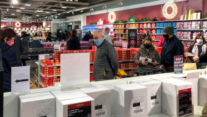 December 2020 shoppers queueing for Marks and Spencer food hall and taking Covid precautions