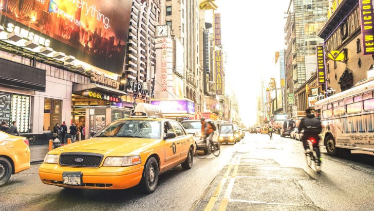 New York yellow taxi cab and everyday life near Times Square in Manhattan downtown before sunset - Intersection of 7th Avenue with 42nd Street